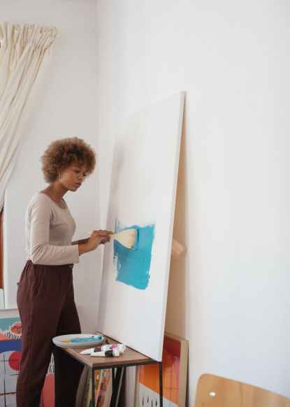 photo of woman painting with blue paint